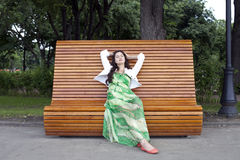 Brunette sitting on a bench Stock Photos