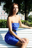 Brunette sitting on a bench Stock Image