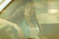 Brunette sitting in car behind closed window, tinted photo. Brunette with long hair sitting in car behind closed window, tinted photo Stock Images