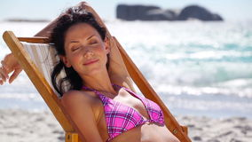 Brunette sitting on a deck chair. On the beach stock video footage