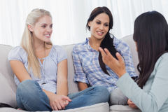 Brunette sitting on floor chatting with friends Royalty Free Stock Image