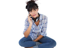 Brunette sitting on the floor with headphones calling someone Royalty Free Stock Photography