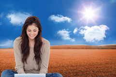 Brunette sitting on floor using laptop Stock Photo
