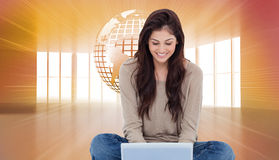 Brunette sitting on floor using laptop Royalty Free Stock Images