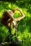 Brunette sitting on green grass Stock Image
