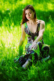 Brunette sitting on green grass Stock Photography