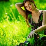 Brunette sitting on green grass Stock Images