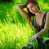 Brunette sitting on green grass stock photo