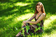 Brunette sitting on green grass stock photos