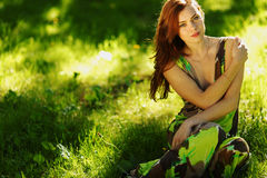 Brunette sitting on green grass Royalty Free Stock Photography