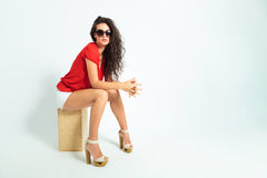 Brunette sitting with hands together wearing sunglasses Stock Photos