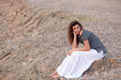 Brunette sitting and looking at camera. Brunette woman sitting on the stone and looking at camera Royalty Free Stock Photography