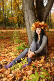Brunette is sitting near tree at the autumn forest Stock Image