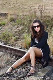 Brunette sitting on rail close Stock Image