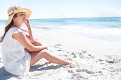 Brunette sitting in the sand and looking at the sea Stock Photo
