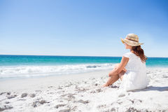 Brunette sitting in the sand and looking at the sea Royalty Free Stock Image