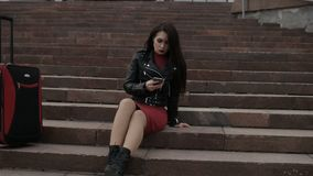 Brunette is sitting on stairs stock video footage