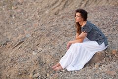 Brunette sitting on the stone. And looking far away Stock Image