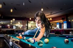 Brunette is sitting on table and playing billiards. stock image