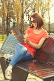Brunette sitting on a wooden bench and using digital tablet Stock Photo