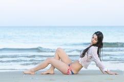Brunette slim body lady wear bottom bikini and wet white shirt lying back on sand Stock Photos