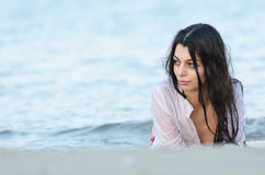 Brunette slim body lady wear bottom bikini and wet white shirt. Lying on the side in the water looking away Stock Images