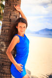 brunette slim girl in blue closeup leans on palm against sea Stock Images