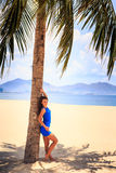 brunette slim girl in blue closeup leans on palm against sea Stock Photos