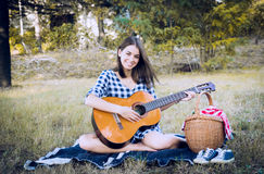 Brunette smiles at camera while playing classic guitar Stock Photography