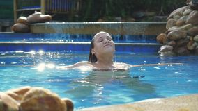 Brunette smiles woman enjoys water in swimming pool in slow motion on sunny day while vacation with beautiful sun stock video