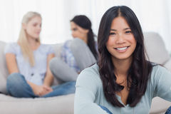 Brunette smiling at camera with her friends behind her. At home on the couch Stock Images