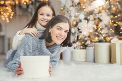Brunette smiling female adult and her beautiful adorable small kid in white sweater being in living room, hold present, going to c stock photography