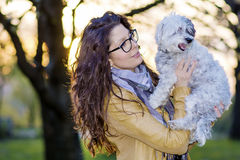 Brunette smiling woman hugging  her white  dog outdoor Stock Image