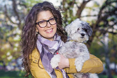 Brunette smiling woman hugging  her white  dog outdoor Stock Photo