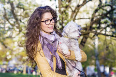 Brunette smiling woman hugging  her white  dog outdoor Stock Photos