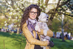 Brunette smiling woman hugging  her white  dog outdoor Royalty Free Stock Photography
