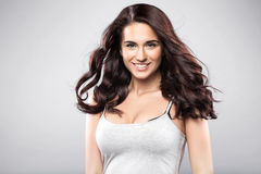 Brunette smiling woman in t-shirt. Beautiful caucasian brunette woman with long shiny brown hair and clean skin. Portrait of a fashion model in studio Stock Image