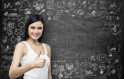 Brunette smiling woman with thumb up gesture. Business icons are drawn on the black chalk board on the background. Stock Photos