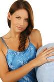 Brunette soñoliento con la almohadilla azul sobre blanco foto de archivo