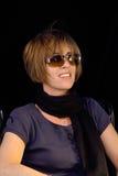 Brunette sonriente en un fondo negro Foto de archivo