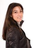 Brunette sonriente en una chaqueta de cuero Foto de archivo libre de regalías