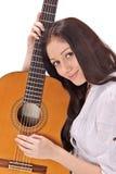 Brunette sonriente joven con la guitarra acústica foto de archivo