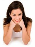 Brunette sorridente sui suoi gomiti Fotografie Stock