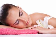 Brunette spa woman in towel on head. Beautiful brunette spa woman lying on towel in spa salon stock photos