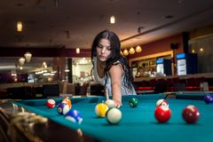 Brunette is spending time playing American billiards. royalty free stock images