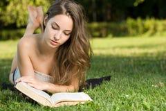 Brunette splendido che legge un libro nella sosta. Fotografia Stock