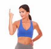 Brunette sporty female in shorts pointing up Royalty Free Stock Image