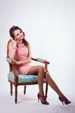 Brunette in the spring image sits on a chair in baroque style an Stock Photography