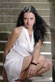 Brunette squatting on a stairway [1] Royalty Free Stock Photos