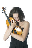 Brunette stands and holds violin in studio against white backgro Royalty Free Stock Photo